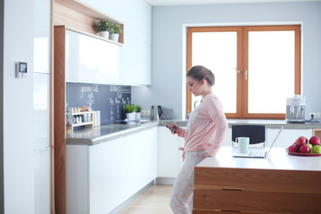 Woman using mobile phone standing in modern kitchen.