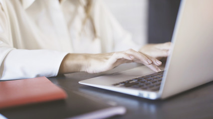Close up of a woman wearing a white shirt typing and using a laptop touchpad in an office. Businesspeople concept.