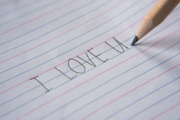 """handwriting using pencil on a paper.write """"i love you"""""""