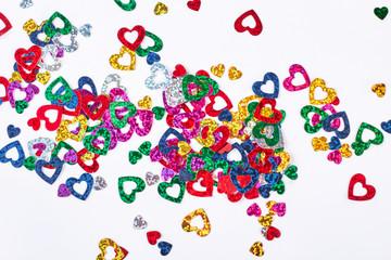 Shiny heart paper confetti. Many glittering multicolored paper hearts confetti on white background. Wedding or Valentine day decoration.