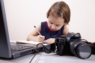 Business plan for photographer and ideas for writing in a notebook concept. Little cute girl thinking about work plan. Humorous image.