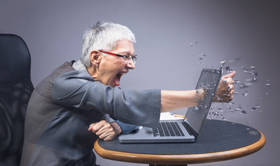 Crazy enraged senior business woman punching through her laptop, frustrated because it doesn't work properly
