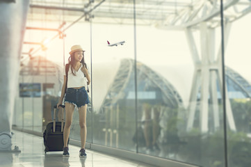 Young woman is standing near window at the airport and watching plane before departure. She is standing and carrying luggage.