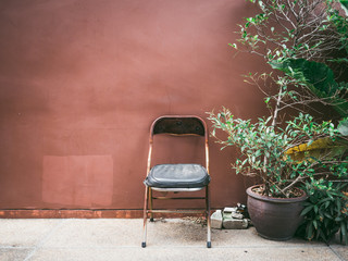 Old cheap rusty chair with plant by grunge brown wall.
