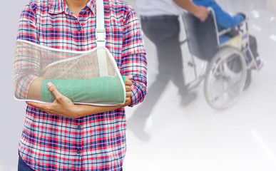 broken arm with green cast and arm sling isolated on blurred background young man pushing a wheelchair and seniors woman sitting in wheelchair