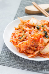 Kimchi cabbage. Korean appetizer on white plate, vertical