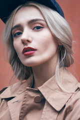 A young beautiful blonde woman is walking and enjoying small urban street in Shanghai. She is wearing nice long brown coat and black hat. Her gorgeous face is accentuated by a dark red lipstick.