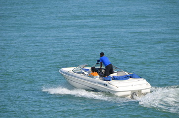 Couple enjoying an afternoon cruise in a motor boat on the florida intra-coastal waterway near Miami Beach.