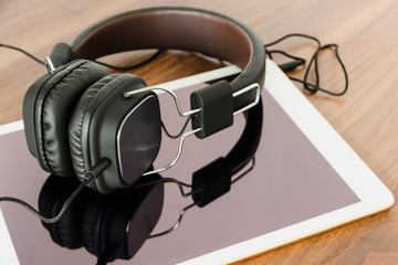 Smartphone and headphone on wooden background for listen to music