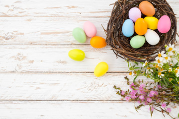 Colorful Easter eggs in nest with flower on rustic wooden planks background in white paint . Holiday in spring season. vintage color tone style. top view composition.