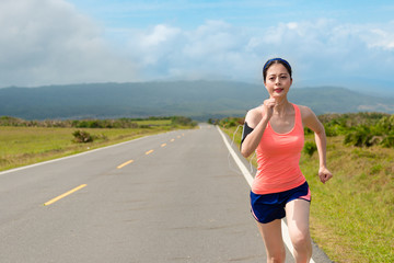 smiling female runner going to countryside road