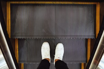 Selfie of  man feet in white sneaker shoes on escalator steps in the shopping mall, top view in vintage style