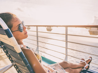 Wall Mural - Cruise ship vacation travel woman relaxing sun tanning lying down on lounger chair on deck balcony. Suntan girl carefree with sunglasses