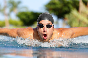Fit swimmer athlete man training butterfly stroke in swimming pool. Professional male triathlete exercising for triathlon ironman swim.