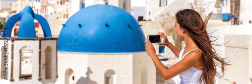 Wall mural Travel tourist taking phone picture of Santorini Blue dome church, touristic attraction in Europe, Panoramic banner. European vacation banner. Woman taking smartphone photo of famous destination.