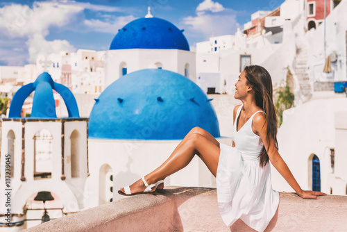 Wall mural Travel luxury Europe vacation woman at Blue Dome Church famous tourist attraction european destination in Oia, Santorini, Greek islands, Greece.