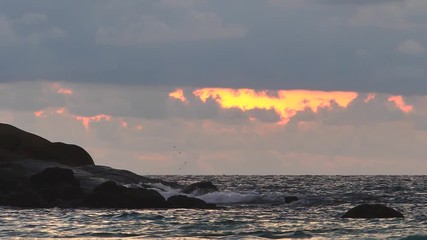Wall Mural - Sea shallow water incoming waves with foam and splashes in slow motion on sunset background