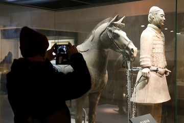A visitor takes a picture of a cavalryman with his saddled War-horse at the Museum of Qin Terracotta Warriors and Horses in Xian, Shaanxi province, in China