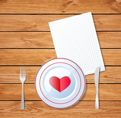 Red heart shape on a plate with knife, fork and empty note pad