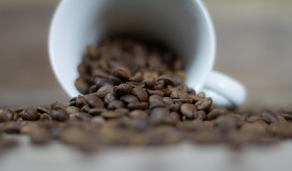 A cup full of coffee beans. Spilled coffee beans on a wooden table