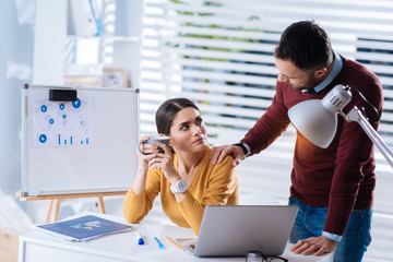 Supporting man. Caring attentive kind man touching the shoulder of his tired upset colleague while visiting her in her big light office