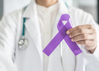 Orchid purple (lavender) ribbon awareness in doctor's hand for (all kinds cancers), Testicular Cancer awareness, Craniosynostosis, Epilepsy, Hodgkin's lymphoma, National Cancer Prevention Month