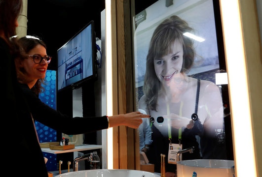 A woman demonstrates the features of a Care OS smart health and beauty hub in a mirror, during CES Unveiled at the 2018 CES in Las Vegas