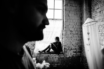 The wife sits on the windowsill and looks out the window, and the foreground silhouette of her husband. Love story. Black and white photo