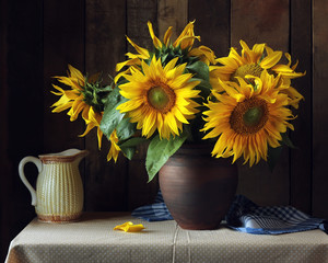 Bouquet of sunflowers in a clay jug on the table.