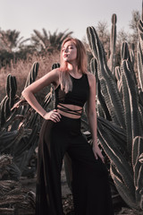 Young blond female in black suit standing near big cactus with eyes shut. Bohemian style. Boho and hippie concept