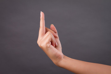 hand pointing up middle finger, concept of rude hand sign or hand gesture, studio isolated