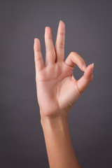 woman hand pointing up okay, yes, accepting hand sign to the side, studio isolated