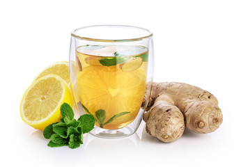 Hot tea with mint, lemon and ginger in a glass with double walls isolated on white background.