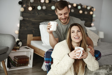 Cheerful couple with coffee enjoying at bedroom