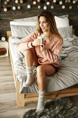 Portrait of woman with coffee sitting on bed .