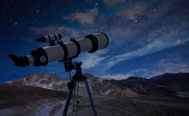 telescope on a tripod pointing at the night sky
