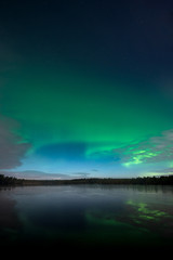 Northern Lights aka Aurora Borealis on midnight sky with reflections on the lake in Kurjenrahka National Park, Finland