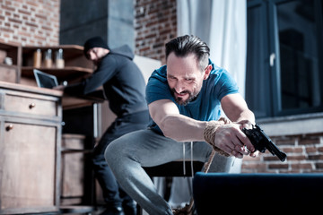 Holding a pistol. Scared panic bearded man sitting with his hands tied and holding the gun while a masked criminal standing behind him and working on the laptop