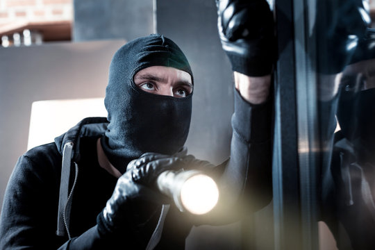 Breaking into. Dark-eyed professional masked burglar opening a window and holding a torch and breaking into the house
