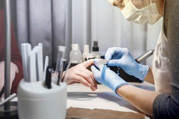 girl does manicure, professional manicure in the salon, removal of gel varnish with help of apparatus, Hands in rubber gloves, protective face mask, manicure of beautiful female hands, working process