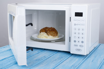 white microwave oven, on a blue wooden surface for heating food