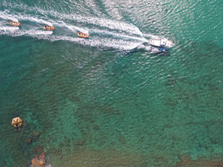 drone view of a yacht yowling 3 boats