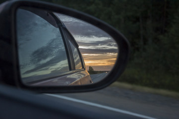 Rear window of auto with view of sundown landscape