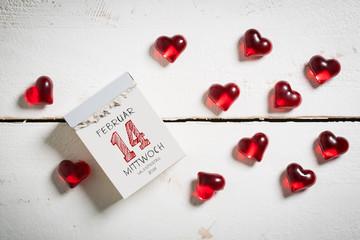 Abreißkalender mit Valentinstag und dekorativen Herzen auf Holzuntergrund