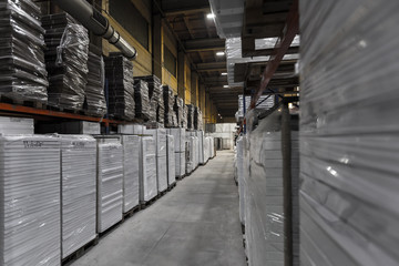 Generic warehouse industrial interior with palettes stacked on shelves. Wide angle view