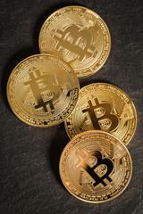 vier Bitcoin Münzen auf Schieferuntergrund