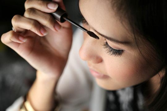 beautiful asia woman Applying makeup - brushing eyebrows.