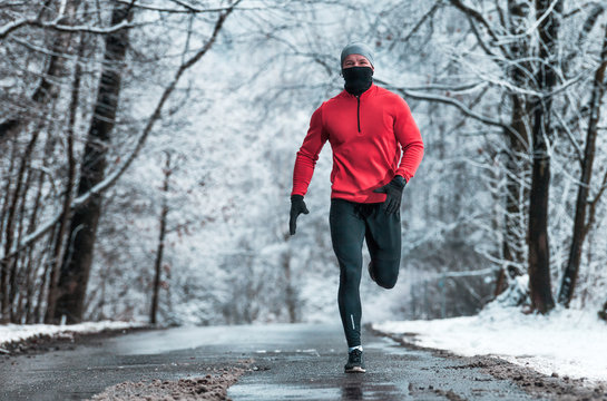 Winter running exercise, runner on road in snowy forest