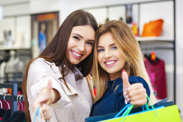 Beautiful young women with shopping bags showing thumbs up.