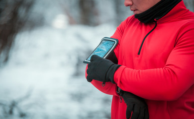 Runner using phone armband wearing warm running clothes, winter exercise outdoor